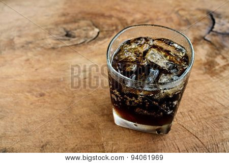 A Glass Of Cola With Ice On Old Wood