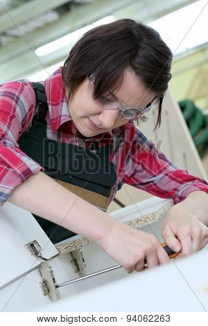 Young woman carpenter assembling furniture
