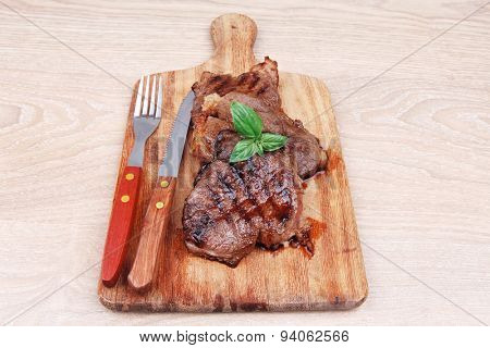 served beef meat barbecue on wooden plate with cutlery