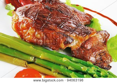 roasted meat served with asparagus on ceramic plate
