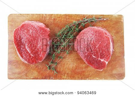 red raw fillet chops : two fresh beef meat chops with small thyme twig on wooden plate . isolated over white background
