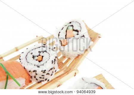 Japanese Cuisine - Maki Roll with Deep Fried Vegetables inside with Sashimi made of Smoked Salmon and Eel. on wooden boats . isolated over white background