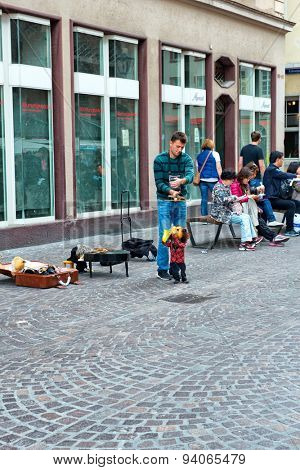 HEIDELBERG, GERMANY - APRIL 26: Man with Saxophone Playing Marionette, Male Busker Puppeteer Performing in Square in Heidelberg, Baden-Wurttemberg, Germany on April 26, 2015