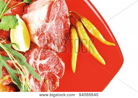 fresh raw beef red meat fillet medallion chunks on red plate isolated over white background