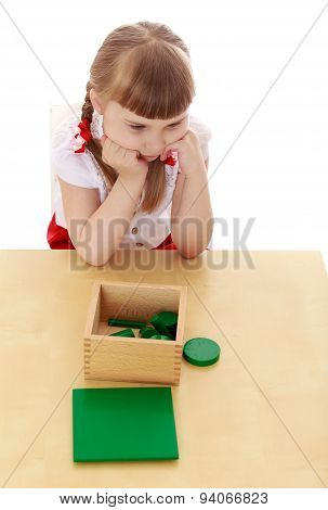Little girl in a Montessori kindergarten studying the material