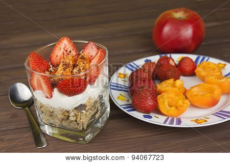 Healthy breakfast with fruit. Homemade yogurt, oatmeal with strawberries, apricots and chocolate.