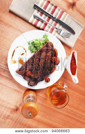 rural design new york meat style beef steak fillet on white plate with hot chili pepper served with tea cup ketchup in Gravy boat pepper mill and cutlery on napkin on wooden table