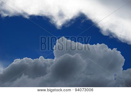 Dark storm cloud comes upon a white cloud