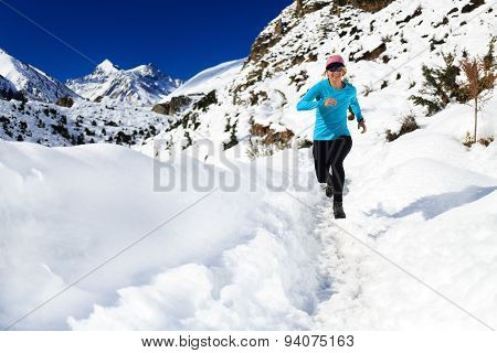 Woman Trail Running On Snow In Winter Mountains