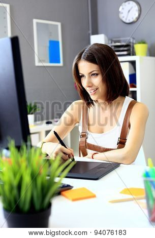 Young Female Designer Using Graphics Tablet While Working With Computer