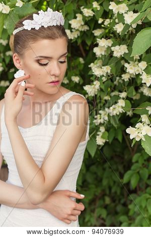 beautiful sexy gentle girl groom near a flowering tree of jasmine in a white dress with tiara and ea