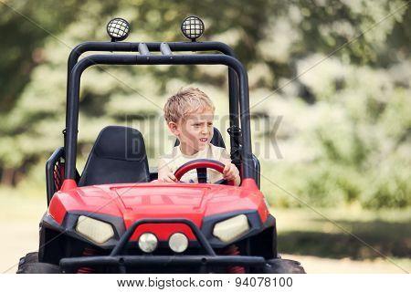 Little Boy Drive A Mini Electric Car In Park