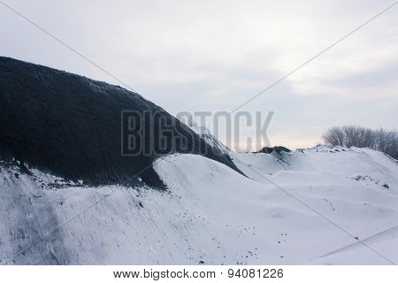 Coal In The Open Warehouse Under The Snow. Donbass, Ukraine