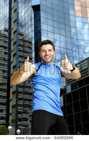 Sport Man Doing Victory Winner Thumbs Up After Running Training In Urban Business District
