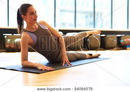 Young Woman Laying On Her Side Doing Leg Exercise