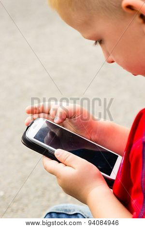 Little Boy Child Playing Games On Mobile Phone Outdoor
