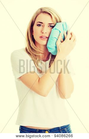 Woman heaving tooth ache, holding ice bag