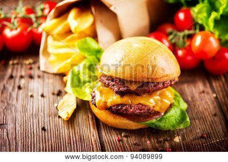 Hamburger with fries on wooden table. Cheeseburger on fresh buns with succulent beef patties and fresh salad ingredients served with French Fries on a wooden table