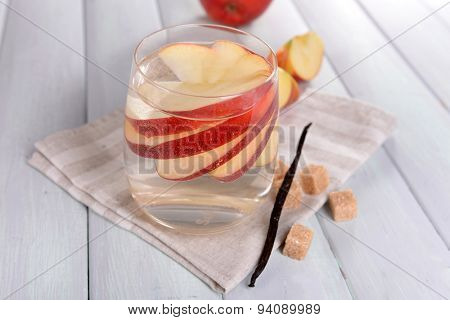 Glass of apple cider with fruits and vanilla stick on table close up