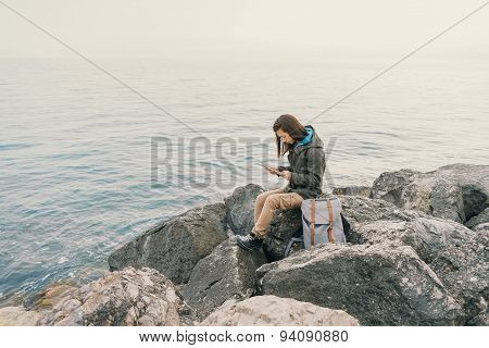 Traveler Working On Digital Tablet On Coast