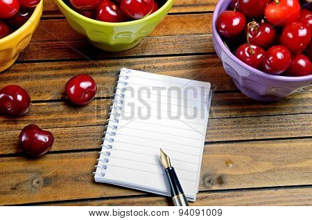 Notebook And Colorful Bowl With Cherries