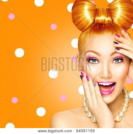 Beauty fashion surprised happy model girl with funny bow hairstyle, red hair, pink nail art and makeup over polka dots orange background. Laughing retro styled young woman
