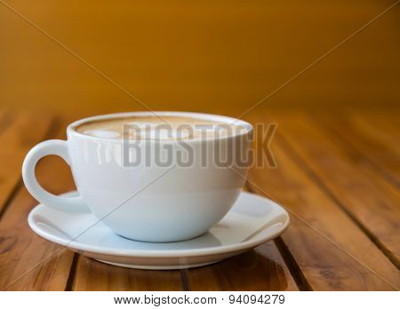 Cup of coffee with heart pattern in a white cup on wood table