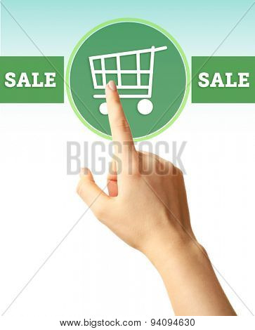 Female hand touching shopping cart symbol