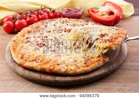 Cheese pizza on wooden cutting board, closeup