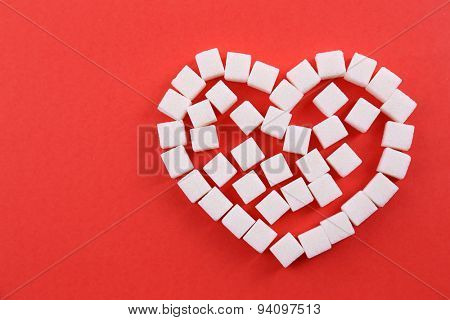 Sugar cubes in heart shape on red background