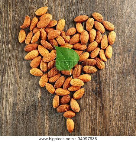 Almonds arranged in heart shape with green leaf on wooden background