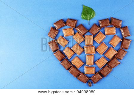 Chocolate pieces arranged in heart shape with green leaf on blue background