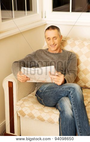 Mature man relaxing with newspaper on the sofa.