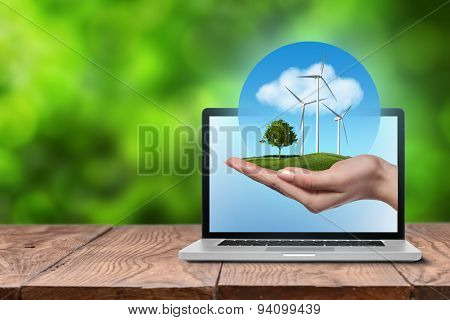 Wind turbines on meadow with tree holds in womans hand against blue sky and clouds in open laptop on wooden table. Worldwide Green energy concept