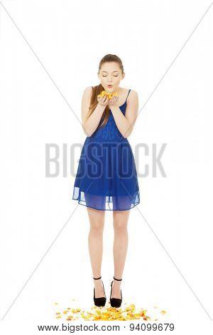 Beautiful teenage woman blowing rose petals.