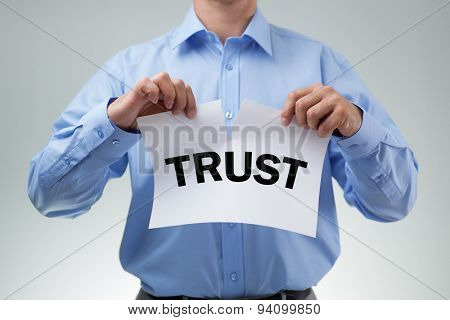 Businessman tearing up sign saying trust concept for infidelity, dishonesty and cheating