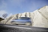picture of arid  - Blue car traveling in a arid landscape of Spain - JPG