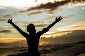 stock photo of open arms  - strong confidence woman open arms under the sunrise at seaside - JPG