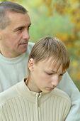 image of sad boy  - Sad father and boy in autumn park - JPG