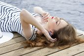 picture of jetties  - fashion woman lying relaxing on wood jetty near blue sea water in summertime - JPG