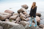 picture of snickers  - Beautiful blond Caucasian teenage girl walking on coastal stones on the lake coast in Finland - JPG