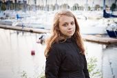 foto of pier a lake  - Portrait of beautiful teenage Caucasian blond girl on the lake coast with pier and yachts on blurred background - JPG