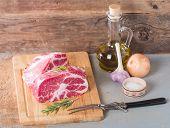 foto of pork chop  - fresh raw pork meat chops on cutting board on old wooden background - JPG