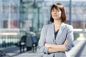 image of close-up middle-aged woman  - Close up portrait of a professional business woman standing with arms crossed - JPG