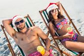 stock photo of couple sitting beach  - happy couple smiling at the beach - JPG