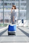 image of walking away  - Full length portrait of a business woman walking away with travel bag and mobile phone - JPG