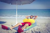 stock photo of rubber mask  - Man lying on the beach with flippers and rubber ring on a sunny day - JPG