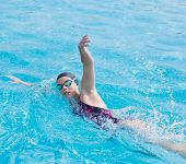 picture of crawling  - Young girl in goggles and cap swimming front crawl stroke style in the blue water pool - JPG