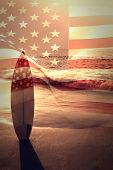 image of united we stand  - Digitally generated united states national flag against surf board standing on the sand - JPG