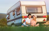 foto of campervan  - Beautiful young couple in front of a camper van on a summer day - JPG